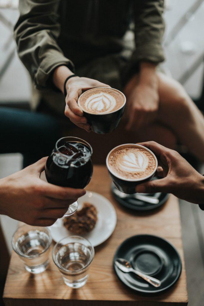 Drei Personen, die sich mit Kaffee bzw. Cappuccino zuprosten