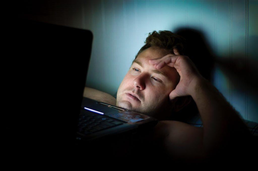 Mann starrt auf Laptop