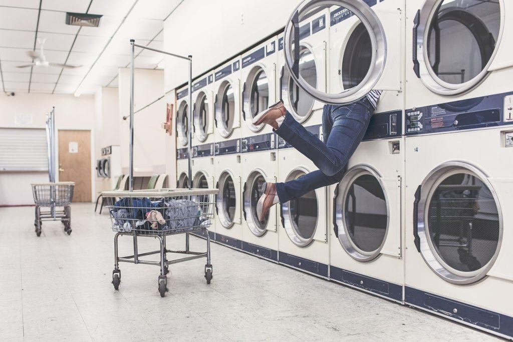 Frau steckt mit Kopf in Waschmaschine