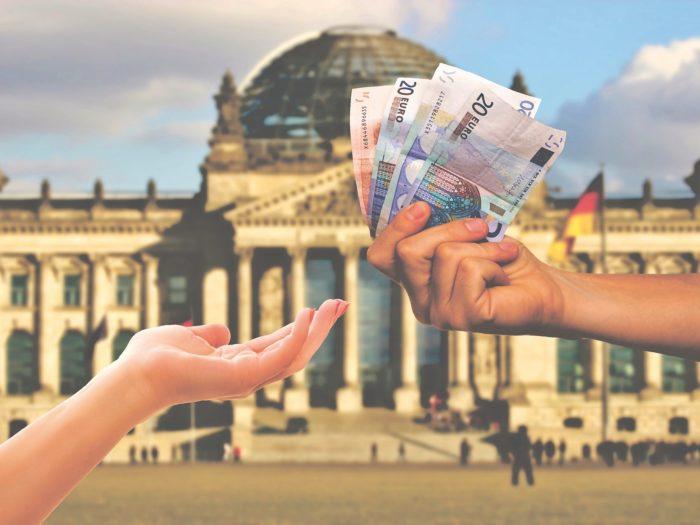 Hand gibt anderer Hand Geld vor dem Reichstagsgebäude