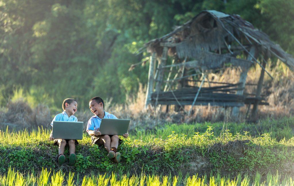 Jungen lachen auf einer Wiese mit Laptops